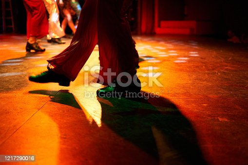 Legs from a group of tap dancers in costume on stage