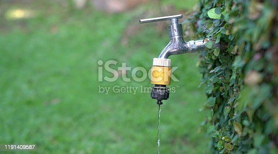 Exterior tap water dripping. Save water or hot summer concept.