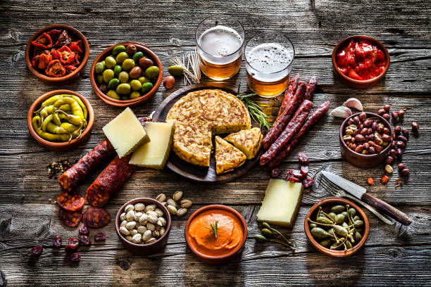 tapas and beer: typical spanish food shot on rustic wooden table - pimento cheese stock photos and pictures