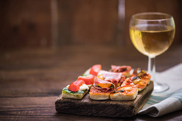 tapas and wine served on wooden board - Photo