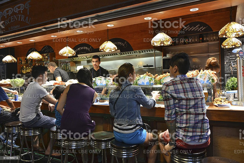 Tapas Bar Barcelona, Spain - August 21, 2014: customers seated at a tapas bar at La Boqueria market in Barcelona, Spain. The market is one of the oldest in Europe and a popular tourist attraction. Appetizer Stock Photo
