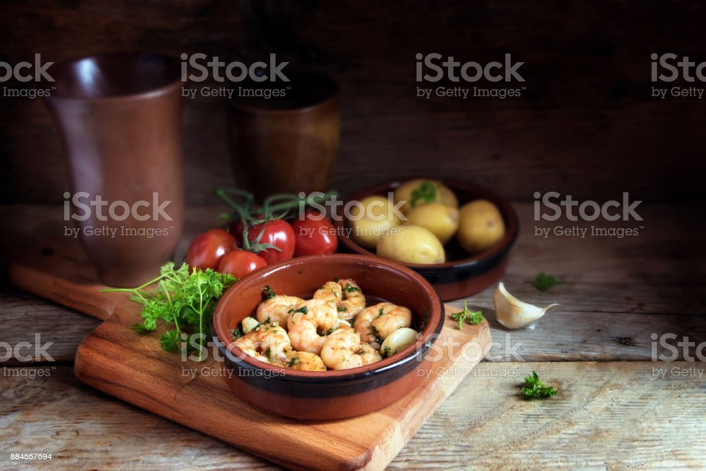 Tapas bowl with shrimps or prawns in garlic olive oil, potatoes, tomatoes and herbs on a rustic wooden table, spanish appetizer, dark background with cop space stock photo