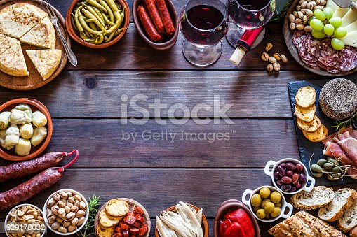 Top view of a wooden table with a large variety of spanish tapas arranged all around the border making a frame and leaving useful copy space for text and/or logo at the center. The composition includes  two wine glasses, spanish tortilla, pickles, cheese, chorizo, bread, peanuts, pistachios, salami, prosciutto, jalapeño peppers, anchovies and others. DSRL studio photo taken with Canon EOS 5D Mk II and Canon EF 100mm f/2.8L Macro IS USM