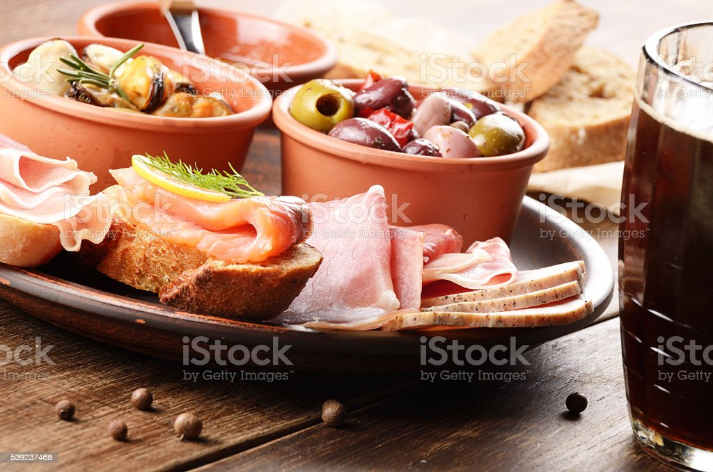 Tapas of salmon, mussels, jamon and olives with beer royalty-free stock photo