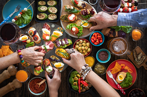 Top view of hands at the dinner table with lots of tapas