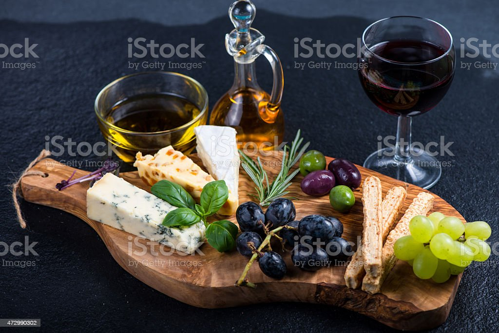 Tapas style appetizer of cheese and grapes on rustic board stock photo