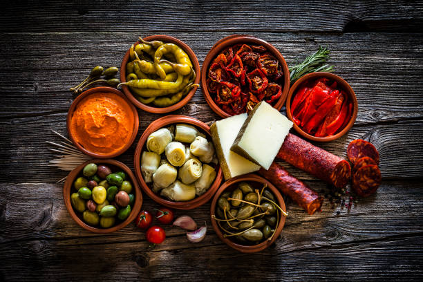 tapas: typical spanish food shot from above on rustic wooden table - pimento cheese stock photos and pictures