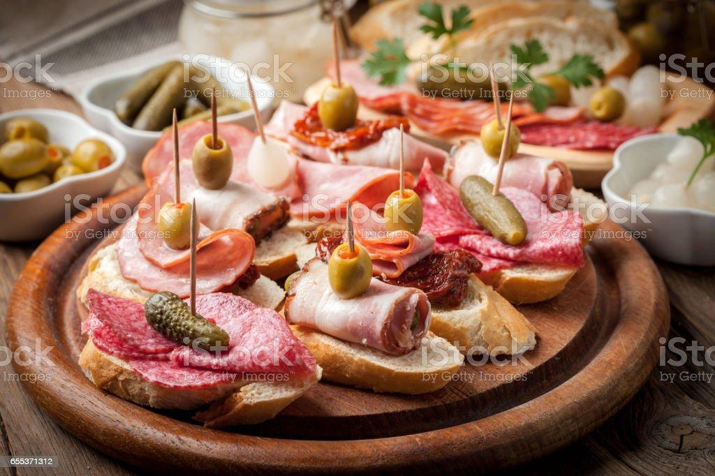 Tapas mit in Scheiben geschnittene Wurst, Salami, Oliven und Petersilie. – Foto