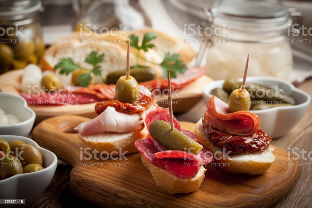 Tapas with sliced sausage, salami, olives and parsley. – Foto