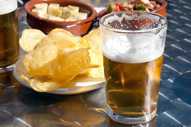 Tapas y cerveza, potato chips and fresh beer in Spain stock photo