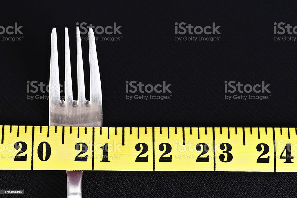 Tape measure and fork on black: dieting for slimness stock photo
