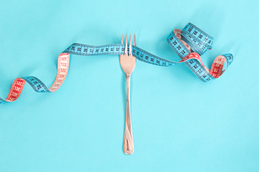 istock Tape measure around a fork as concept for diet. Fork are wrapped in blue measuring tape on blue background. 1125730286