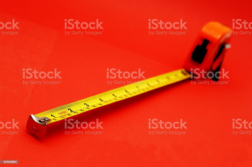 tape measure extended against vibrant red royalty-free stock photo