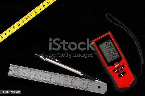 949860388istockphoto Tape measure, laser distance meter and metallic ruler with pencil on black background 1132990043