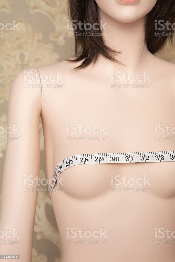 Tape measure on a mannequins breasts 免版稅 stock photo