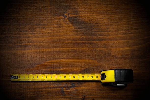 Tape Measure on a Wooden Work Table Yellow and black tape measure on a wooden and empty work table with dark shadows tape measure stock pictures, royalty-free photos & images