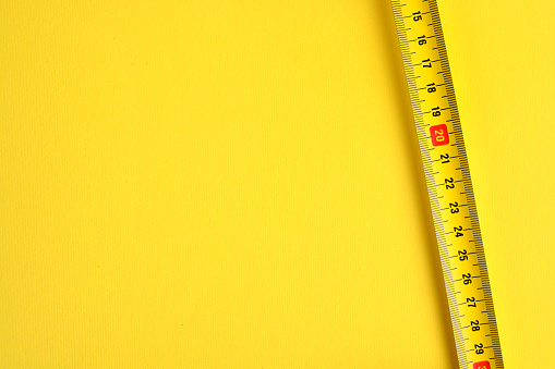 istock Tape measure scale on a yellow background. Copy space. 1175080168