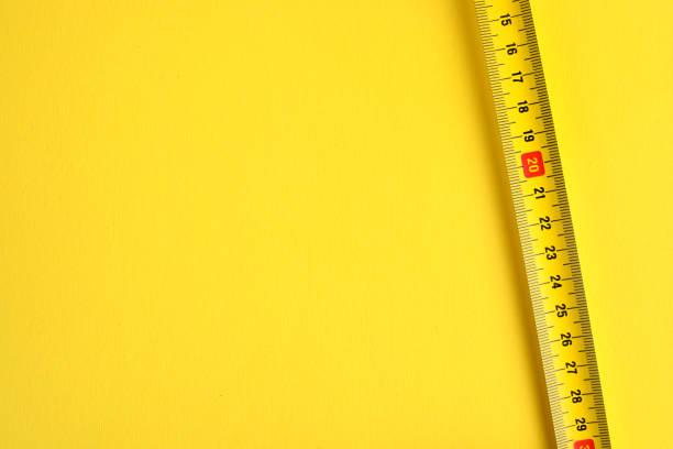 노란색 배경에 줄자 측정 눈금. 공간을 복사합니다. - 측정 장치 뉴스 사진 이미지