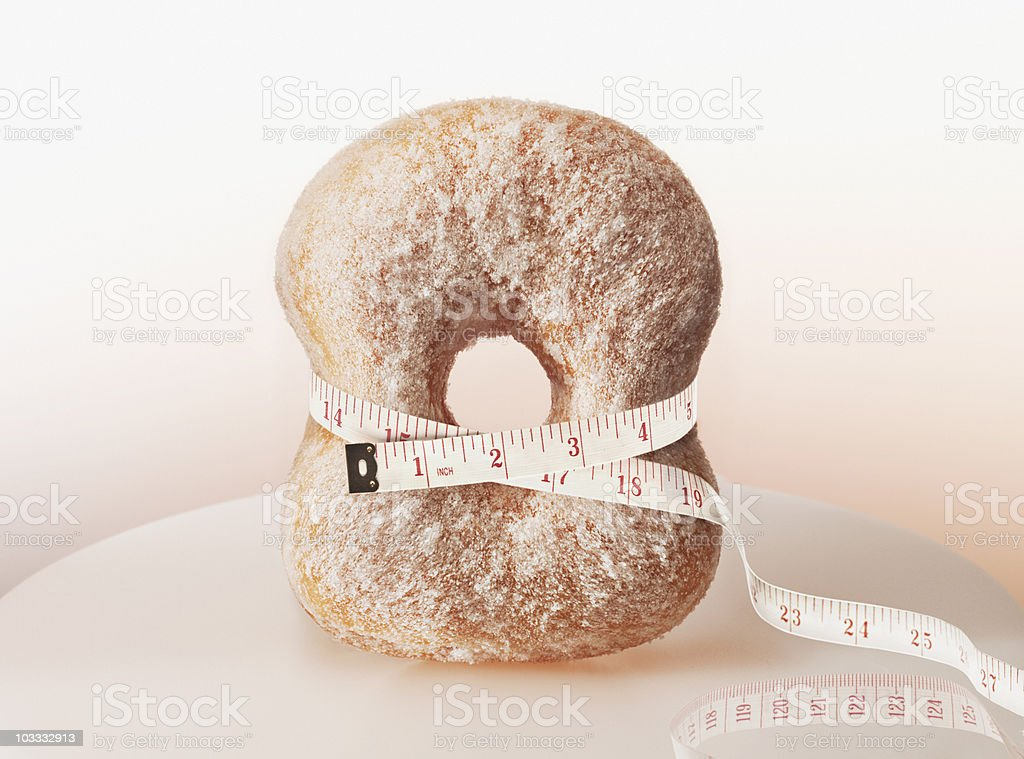 Tape measure squeezing donut stock photo