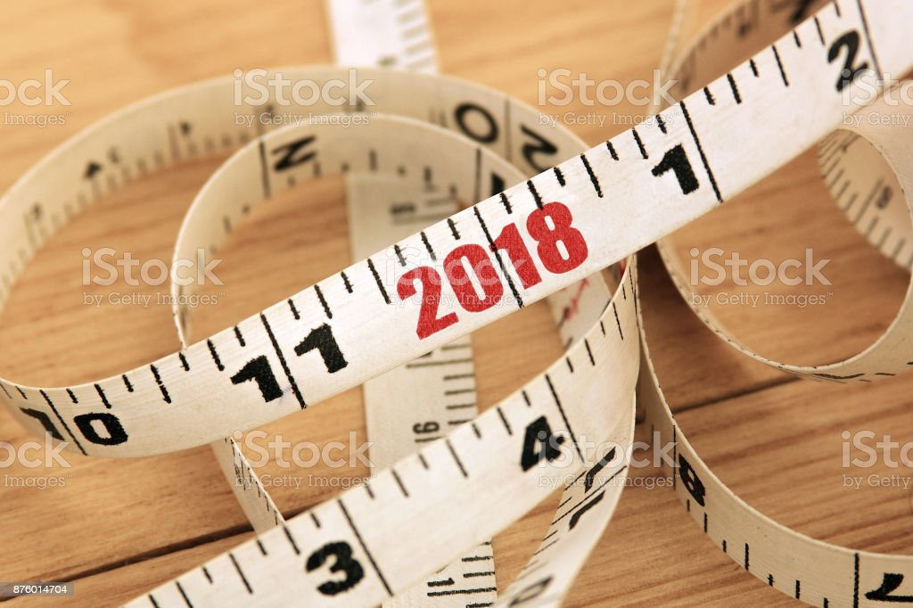Tape measure with red numbers 2018 on wooden desk. New Year 2018 concept. stock photo