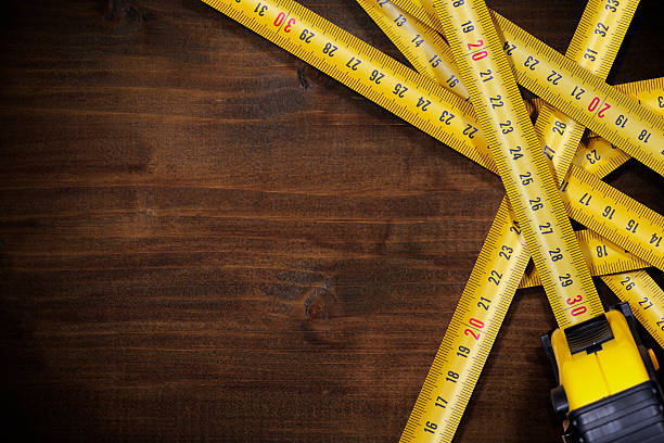 Tape Measures on Brown Wooden Background stock photo