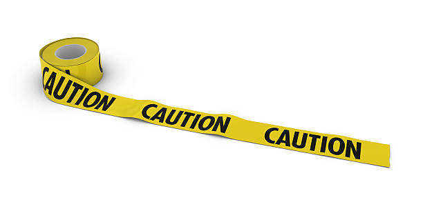 CAUTION Tape Roll unrolled across white floor stock photo