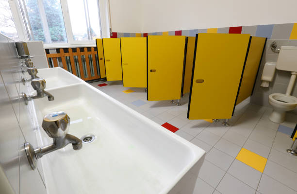 taps of washbasin and yellow doors in the bathroom of a nursery stock photo