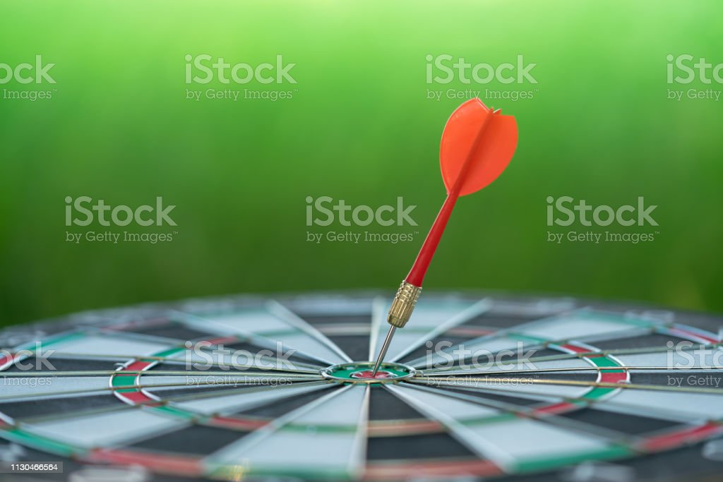 Red dart arrow hitting in the target center of dartboard with green...