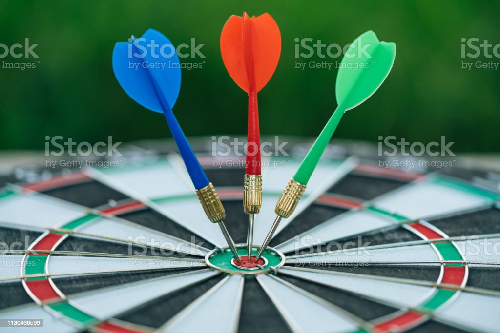 Blue, Red and Green dart arrow hitting in the target center of...