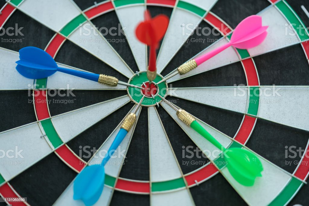 Red dart arrow hitting in the target center of dartboard with other...