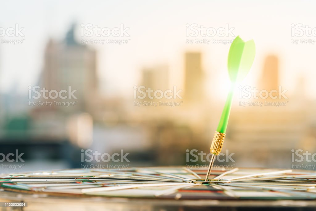 Green dart arrow hitting in the target center of dartboard with city...