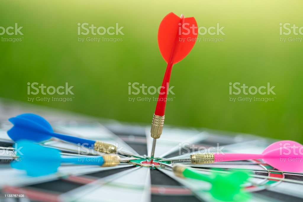 Red dart arrow hitting in the target center of dartboard with city...