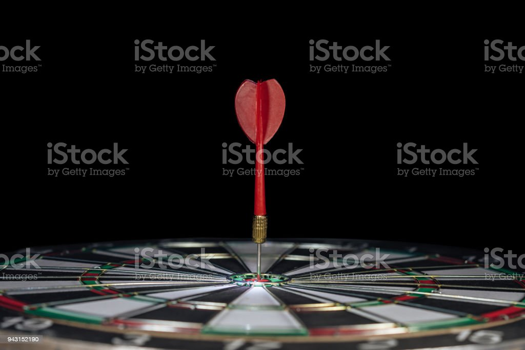 Red dart arrow hitting in the target center of dartboard with black...