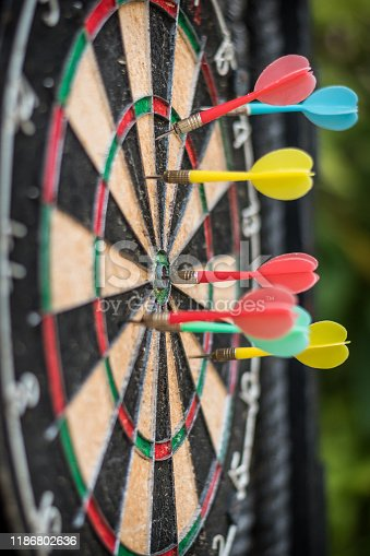 istock Target dart game with one win arrow hit on middle point spot and many missing for competitive business marketing concept 1186802636