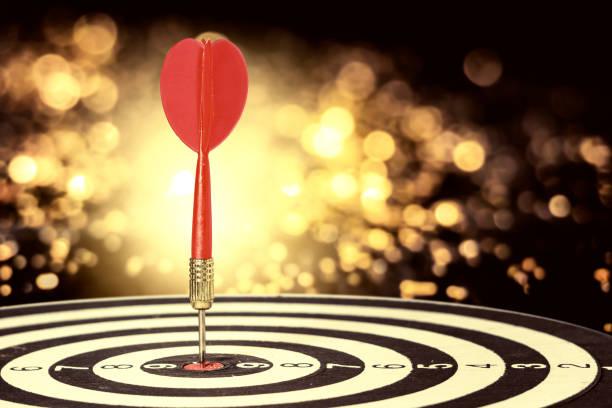 target dart with arrow over blurred bokeh background ,metaphor to target marketing or target arrow concept. stock photo