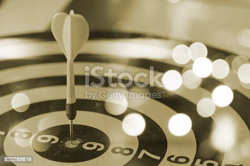 istock target dart with target arrows on the bokeh background and dartboard is the target and goalabstract background to target marketing or target arrow or target business concept 822289816