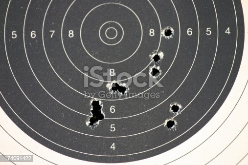 paper target with bullet holes from the gun range