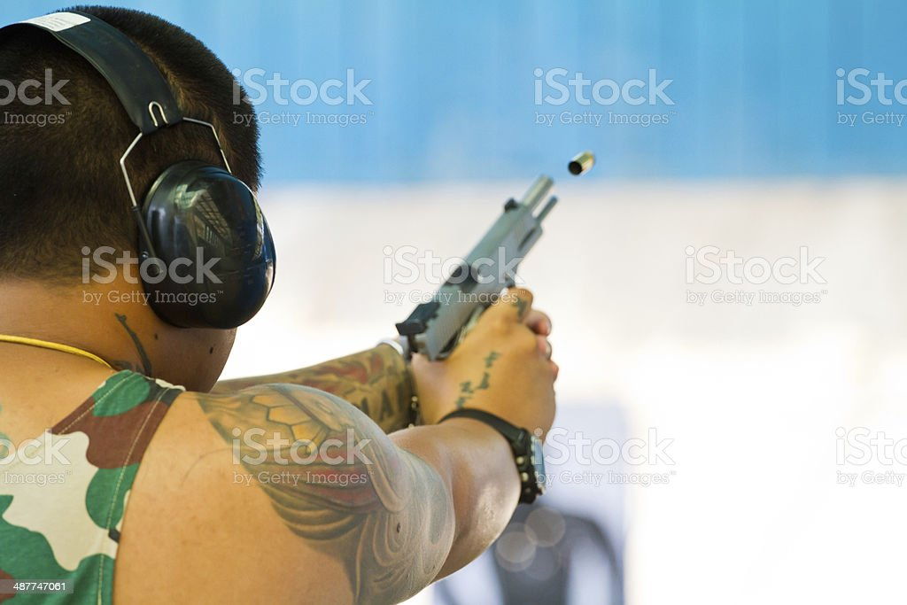 Target practicing with gun In the shooting range