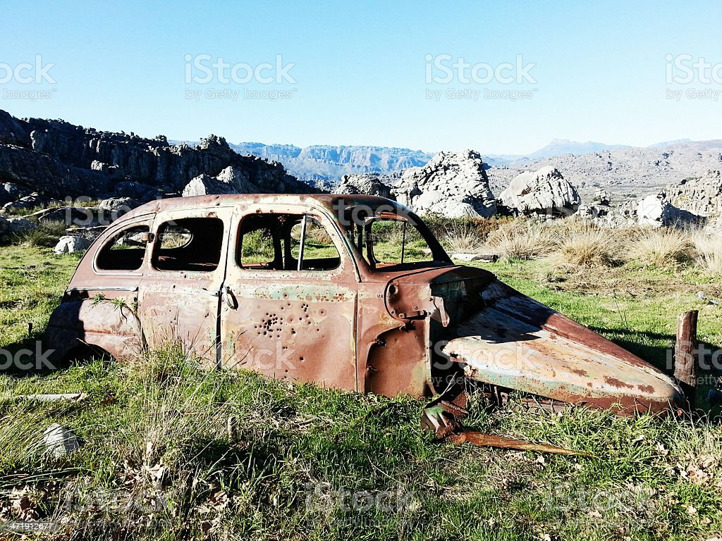 Target practise in the wilderness; bullet-ridden car carcasse stock photo