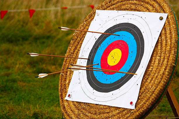Target stand for archery with arrows in it and holes stock photo