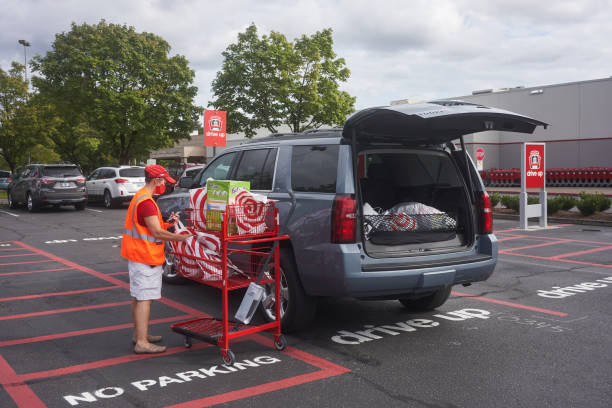 Target Store Drive-up Service Tigard, OR, USA - Sep 19, 2020: A Target store employee brings bagged items out to a customer's car parked in the drive-up area outside the Target Tigard store during the coronavirus pandemic. curbsidepickup stock pictures, royalty-free photos & images