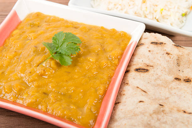 Tarka Dahl Tarka Dahl - Indian yellow split pea curry garnished with coriander and served with pilau rice and chapatis. dal makhani stock pictures, royalty-free photos & images