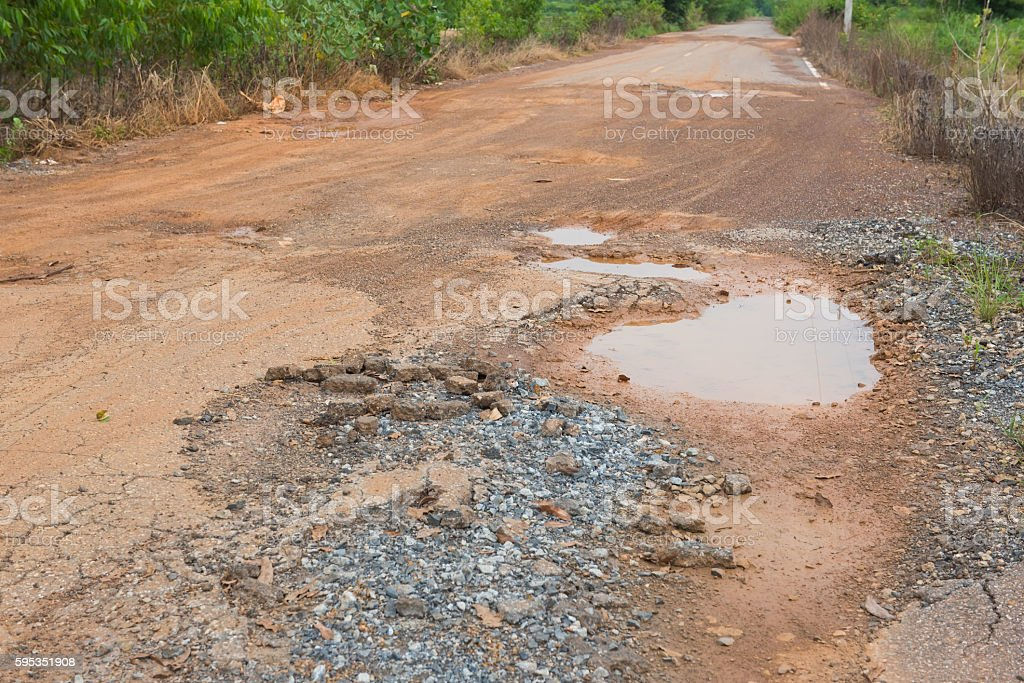 tarmac road in the countryside with potholes and puddles stock photo