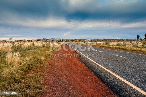 Tarmac road lead to nowhere in Australian desert in stormy cloud