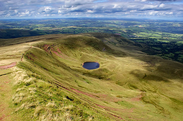 Tarn on the Brecon Beacons near Corn Du A view looking towards a Tarn (small mountain lake) from Corn du, within the Brecon Beacons National Park in South Wales. There is a large amount of clouds with a blue sky background. The scenery is mountainous and very undulating. brecon beacons stock pictures, royalty-free photos & images