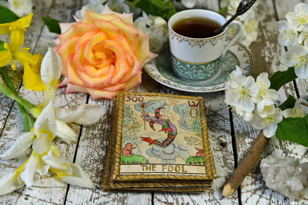 Tarot card Joker with rose and lily flowers on witch altar, fortune telling seance. stock photo