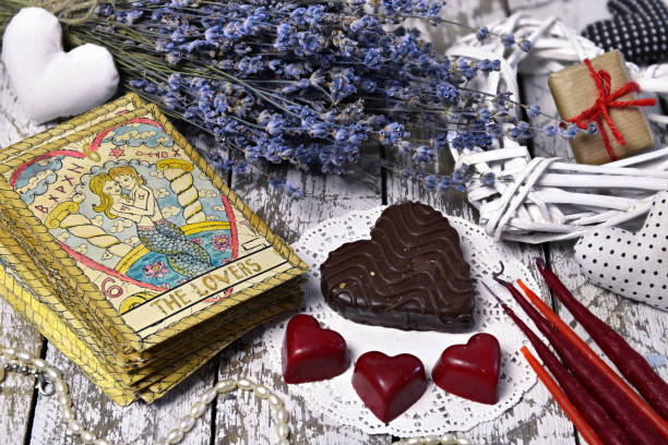Tarot card Lovers, chocolate candies, heart and love symbols, lavender flowers, candles stock photo