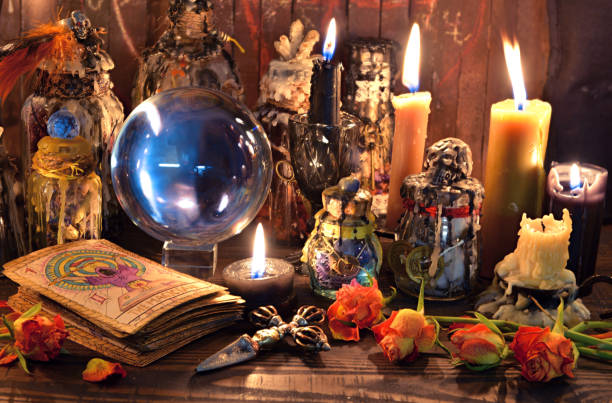 Tarot cards, burning candles, witch magic bottles and crystal ball. stock photo