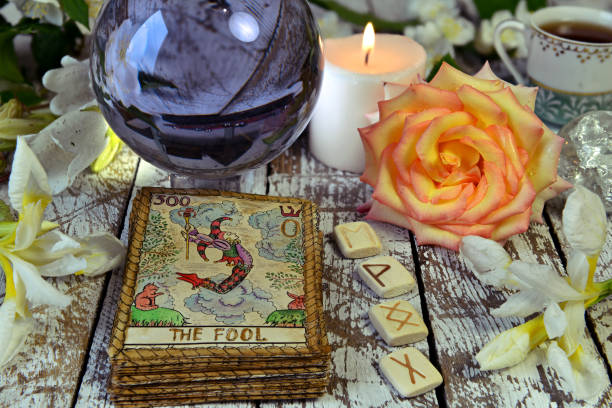 Tarot cards deck, crystal ball, runes and flowers on witch table. stock photo