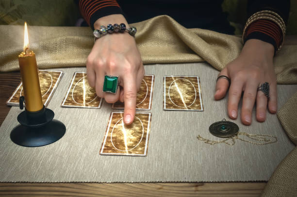 Tarot cards. Future reading concept. Fortune teller desk table. Tarot cards and fortune teller desk table. Future reading. Woman fortune teller shows with her index finger on tarot card. arcane stock pictures, royalty-free photos & images